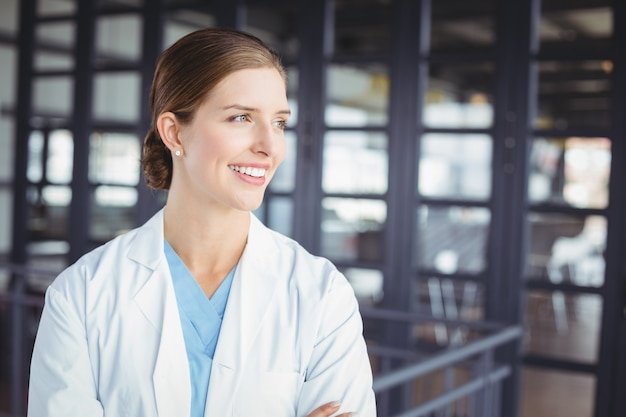 Glimlachende vrouwelijke arts die weg kijkt