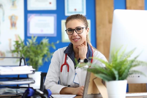 Glimlachende vrouwelijke arts in bureauzitting bij lijst
