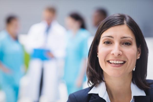 Glimlachende vrouwelijke arts in het ziekenhuispand