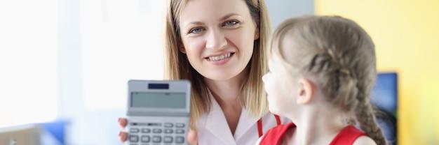 Glimlachende vrouwelijke arts met de rekenmachine van de jonge meisjesholding. medisch verzekeringsconcept