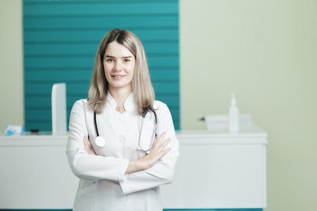 Glimlachende vrouwelijke arts of verpleegster in medisch uniform, stethoscoop op hals
