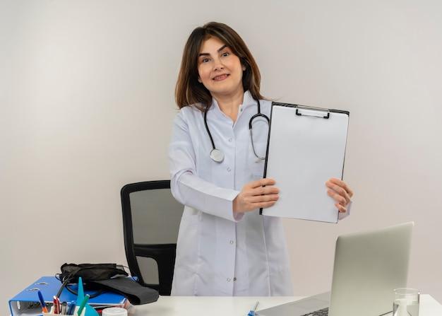 Glimlachende vrouwelijke arts van middelbare leeftijd die het dragen van medische mantel met een stethoscoop draagt ?? die achter bureau werkt op laptop met medische hulpmiddelen die klembord op geïsoleerde witte backgroung met exemplaarruimte houden