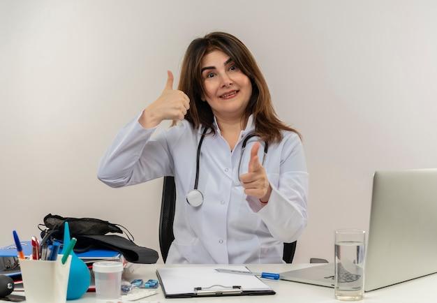 Glimlachende vrouwelijke arts van middelbare leeftijd die het dragen van medische mantel met stethoscoop zittend aan bureau werkt op laptop met medische hulpmiddelen toont u gebaar haar duim omhoog op witte muur