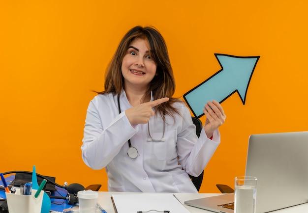 Glimlachende vrouwelijke arts van middelbare leeftijd die medisch kleed met stethoscoop zittend aan bureau werkt op laptop met medische hulpmiddelen houden en wijst naar richtingsteken op oranje muur