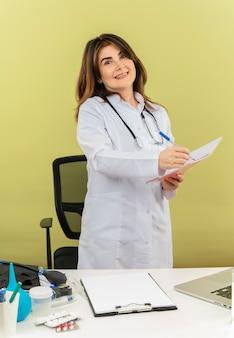 Glimlachende vrouwelijke arts van middelbare leeftijd die medische gewaad met stethoscoop zit aan bureau werkt op laptop met medische hulpmiddelen die pen en notitieboekje met exemplaarruimte houden