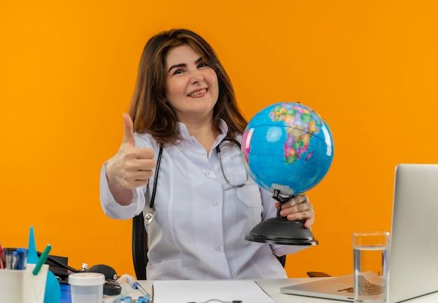 Glimlachende vrouwelijke arts van middelbare leeftijd die medische mantel draagt met een stethoscoop zittend aan een bureau werkt op laptop met medische hulpmiddelen die globe haar duim omhoog houdt op geïsoleerde oranje achtergrond met kopie ruimte