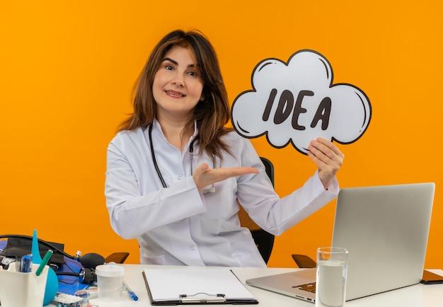 Glimlachende vrouwelijke arts van middelbare leeftijd die medische mantel met stethoscoop zittend aan bureau werkt op laptop met medische hulpmiddelen houden en punten met hand idee zeepbel op oranje muur