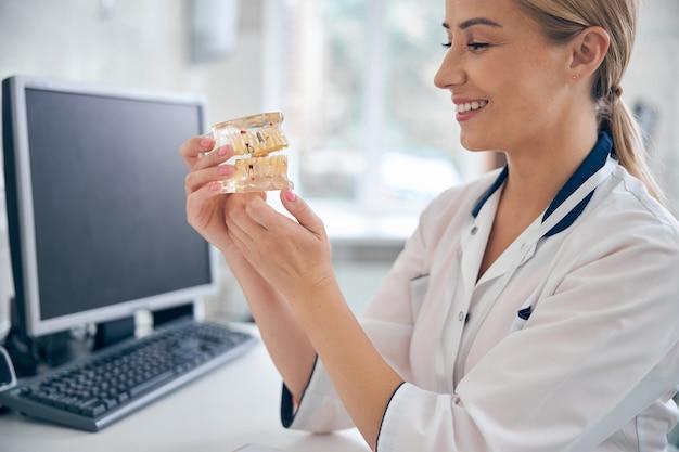 Glimlachende vrouwelijke arts zit aan bureau met computer en houdt kaakmodel vast terwijl hij ernaar kijkt