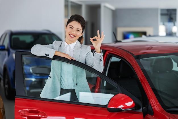 Glimlachende vrouwelijke autoverkoper die op auto leunt terwijl status in autosalon en oke gebaar met hand duwt