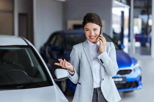 Glimlachende vrouwelijke autoverkoper die telefoongesprek met een cliënt heeft en hem overtuigen om een auto te kopen. auto salon interieur.