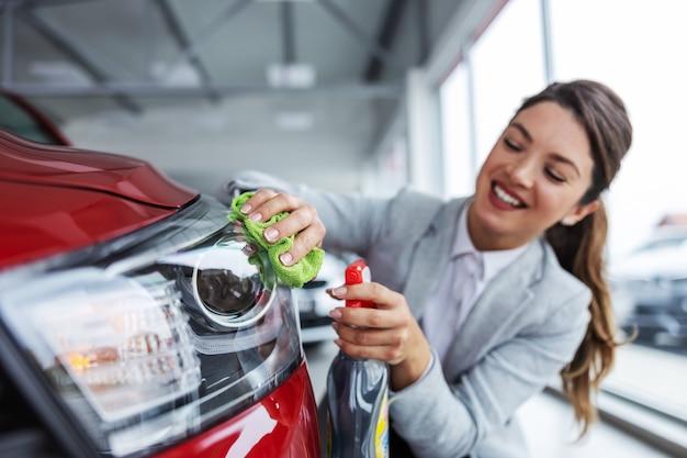 Glimlachende vrouwelijke autoverkoper in kostuum die en auto met wasmiddel hurken afvegen. auto salon interieur.