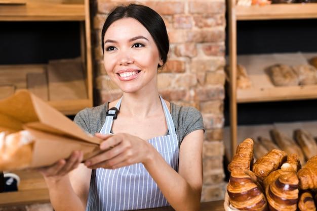 Glimlachende vrouwelijke bakker die verpakt brood geeft aan de klant in de bakkerij