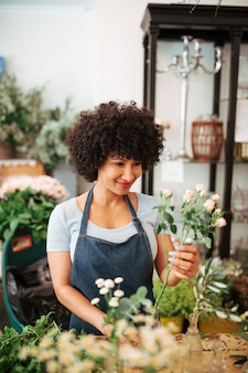 Glimlachende vrouwelijke bloemist die bloemen in glasvaas schikken