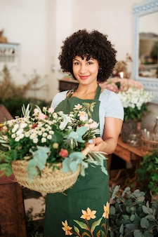 Glimlachende vrouwelijke bloemist die mand van bloemen houdt