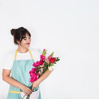 Glimlachende vrouwelijke bloemist met bos van bloemen die zich op witte achtergrond bevinden