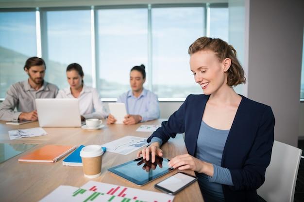 Glimlachende vrouwelijke directeur die digitale tablet in vergaderruimte gebruikt