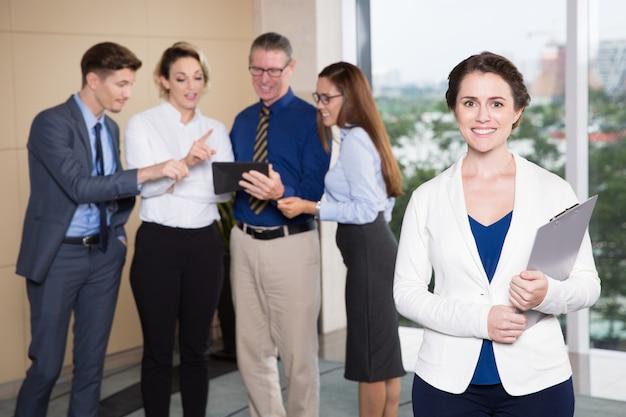 Glimlachende vrouwelijke executive staande voor team