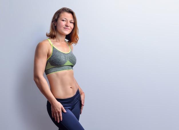 Glimlachende vrouwelijke fitnesscoach in grijze top en zwarte legging met slanke buikspieren poseert op de witte achtergrond, vooraanzicht.
