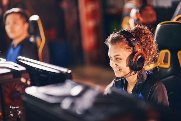 Glimlachende vrouwelijke gamer van gemengd ras die een koptelefoon draagt die online videogames speelt terwijl hij zit