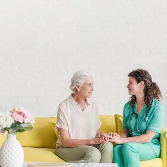 Glimlachende vrouwelijke hogere patiënt en verpleegster die elkaars hand houden