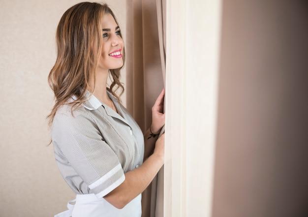 Glimlachende vrouwelijke huishoudster die het gordijn opent