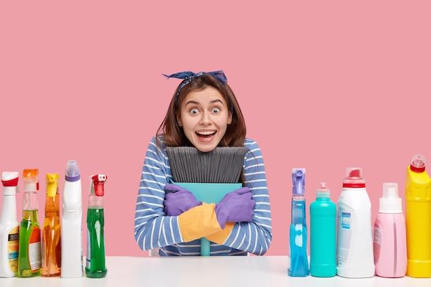 Glimlachende vrouwelijke huishoudster heeft een verbaasde uitdrukking, brede glimlach, draagt de bezem nauw, kruist handen over de borst, draagt rubberen handschoenen, blij met vrije dag