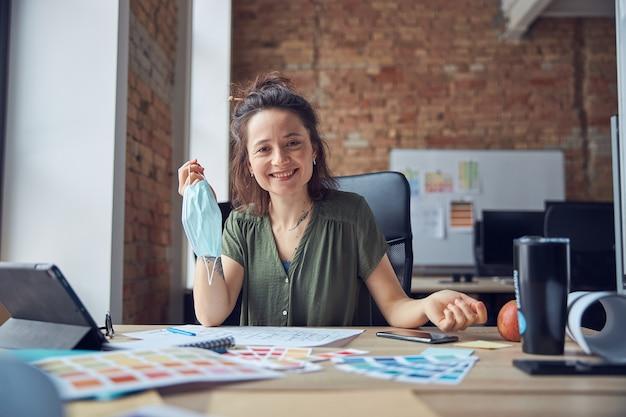 Glimlachende vrouwelijke interieurontwerper die een beschermend masker vasthoudt en naar een camera kijkt die met kleur werkt