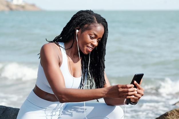 Glimlachende vrouwelijke jogger die rust na de training op het strand en een videogesprek voert met een vriend of familielid