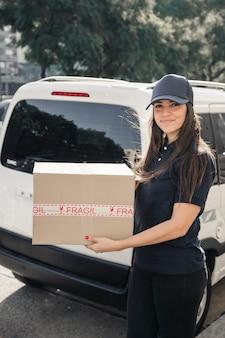 Glimlachende vrouwelijke koerier met pakket die zich vooraan o voertuig bevinden
