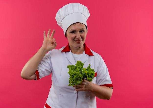 Glimlachende vrouwelijke kok op middelbare leeftijd in de salade die van de chef-kok de eenvormige holding ok gebaar toont