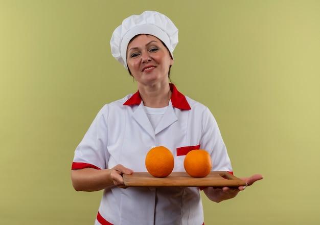 Glimlachende vrouwelijke kok van middelbare leeftijd in de eenvormige oranje van de chef-kok houden op scherpe raad met exemplaarruimte