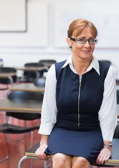 Glimlachende vrouwelijke leraar in de klas