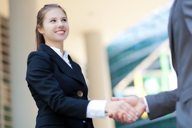 Glimlachende vrouwelijke manager handen schudden