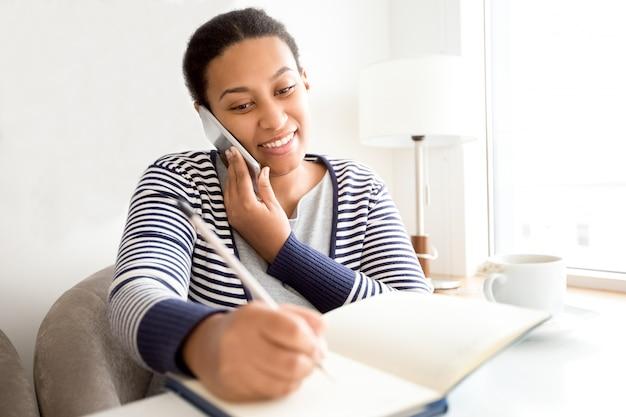 Glimlachende vrouwelijke manager praten met de klant op de telefoon