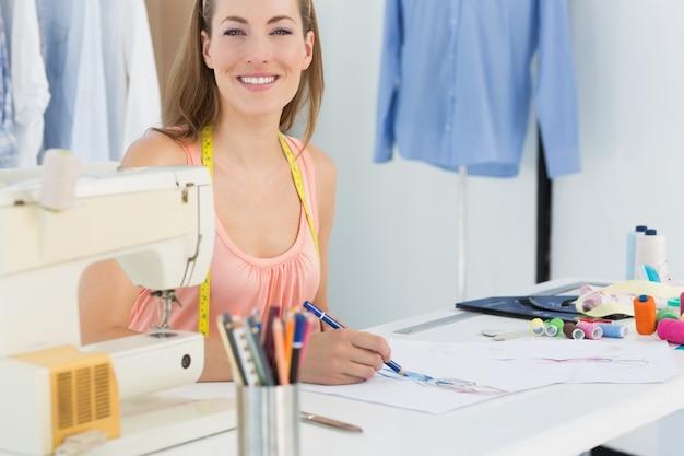 Glimlachende vrouwelijke manierontwerper die aan haar ontwerpen werkt