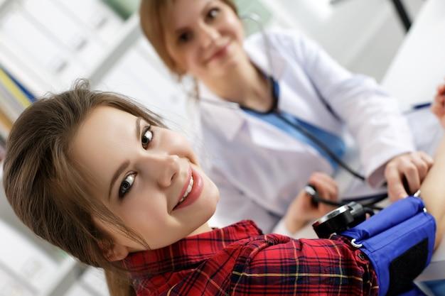 Glimlachende vrouwelijke patiënt die de bloeddruk meet bij het kantoor van de arts van de geneeskunde. gezondheidszorg, gezonde levensstijl en medische dienst of verzekeringsconcept