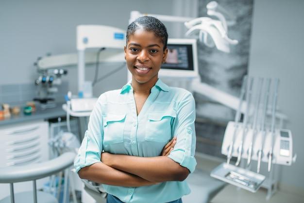 Glimlachende vrouwelijke patiënt in tandkliniek, medische apparatuur op achtergrond. vrouw in tandheelkundekabinet, stomatologie, tandenzorg