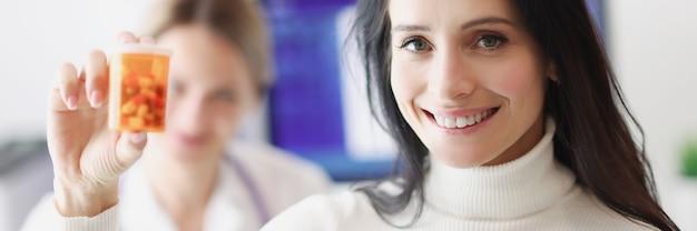 Glimlachende vrouwelijke patiënt met pillen op de achtergrond van de dokter