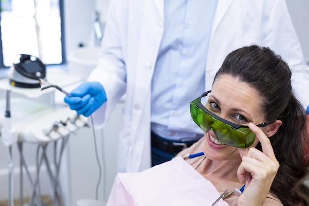 Glimlachende vrouwelijke patiënt zittend op tandartsstoel