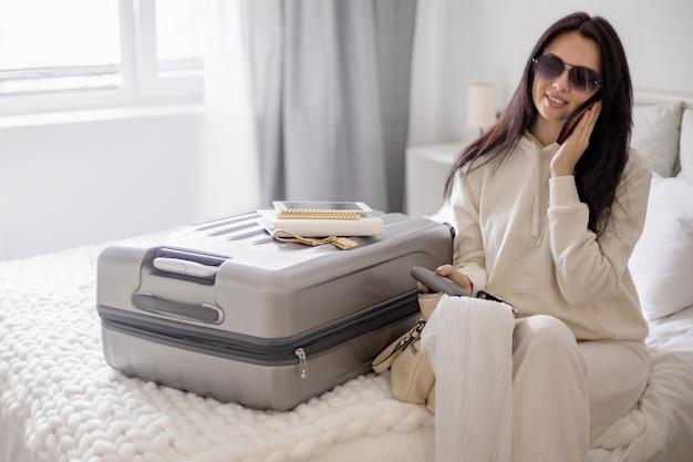 Glimlachende vrouwelijke pratende smartphone gebruiken voordat ze zich voorbereiden om op vakantie of zakenreis te reizen