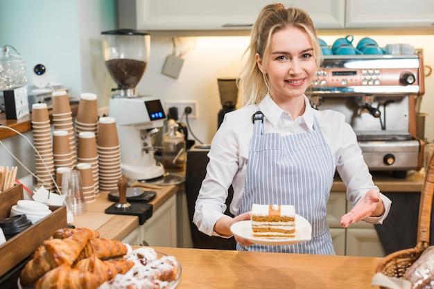 Glimlachende vrouwelijke serveerster die het gebakje in de koffiewinkel aanbieden