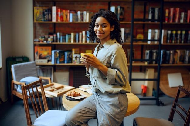 Glimlachende vrouwelijke student in bibliotheekcafé. vrouw met koffie en croissants vormt aan tafel, onderwijs en kennis. meisje studeert op de campus