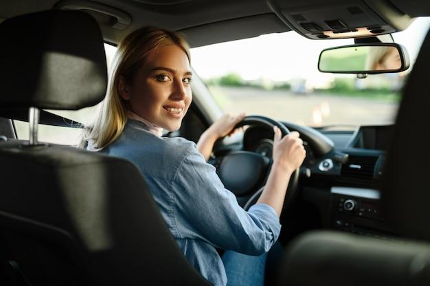 Glimlachende vrouwelijke student in de auto, les in rijschool. man die dame leert voertuig te besturen. rijbewijs opleiding