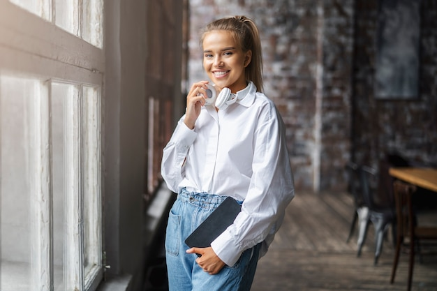 Glimlachende vrouwelijke student in een wit overhemd en draadloze koptelefoon staat voor het raam.
