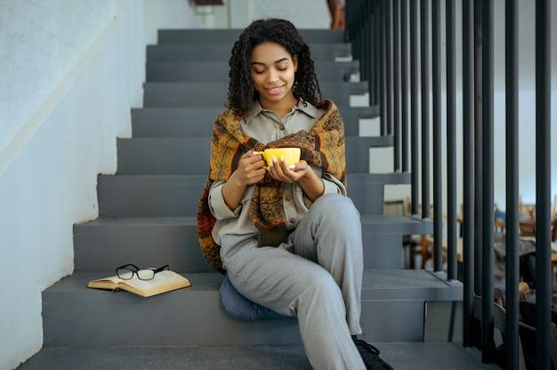 Glimlachende vrouwelijke student met koffie zittend op de trappen in bibliotheekcafé. vrouw met kop, geopend boek en glazen, onderwijs en kennis. meisje studeert op de campus