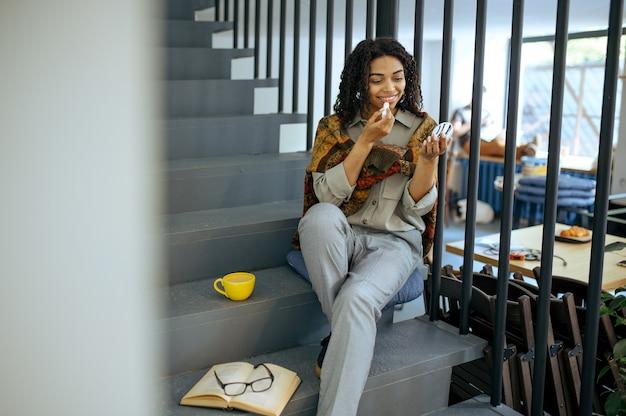 Glimlachende vrouwelijke student met lippenstift, zittend op de trappen in bibliotheekcafé