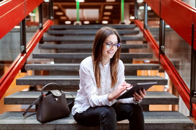 Glimlachende vrouwelijke student met oogglazen en bruin haar die tablet gebruiken terwijl het zitten op de treden