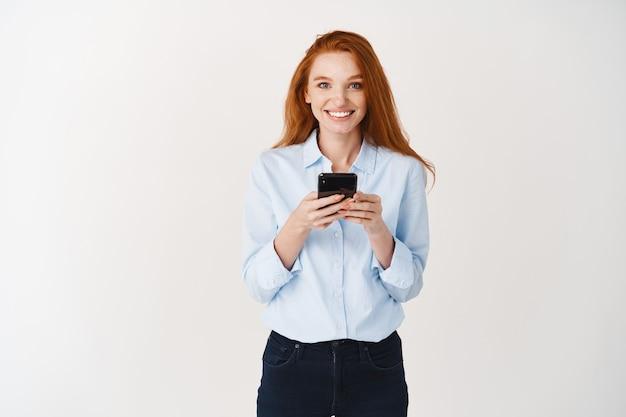 Glimlachende vrouwelijke student met rood haar en blauwe ogen met behulp van mobiele telefoon, blij kijkend naar voren, staande over een witte muur