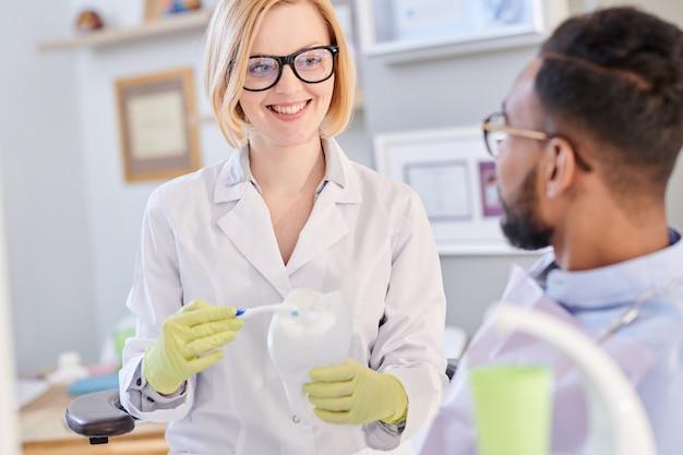 Glimlachende vrouwelijke tandarts holding toothbrush