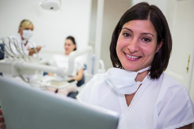 Glimlachende vrouwelijke tandarts in tandkliniek